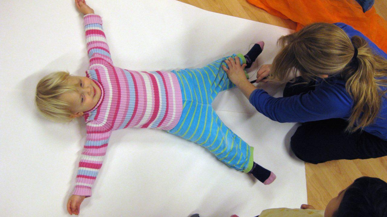Barn får tegnet omriss av kroppen sin