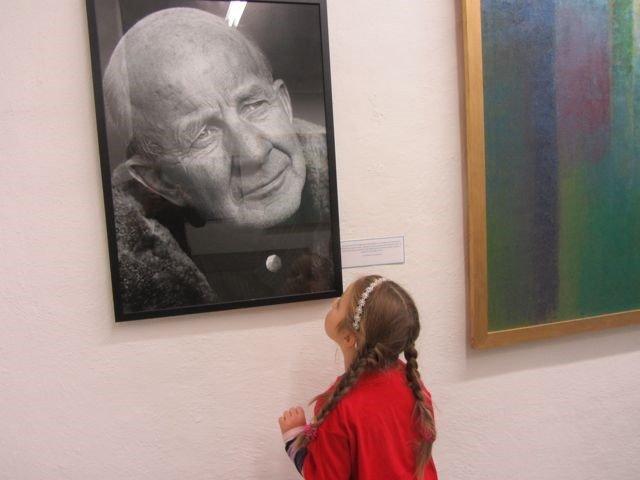 Barn på galleribesøk og studerer portrett av mann i sort/hvitt.