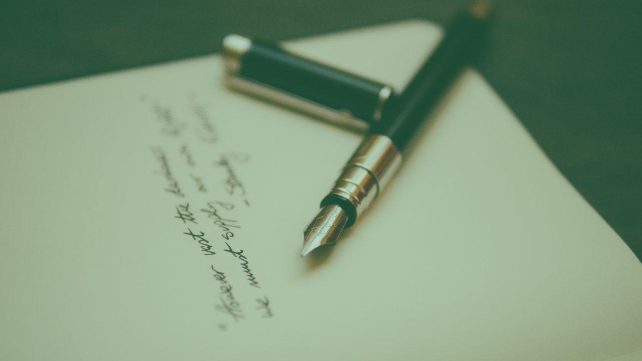Svart fyllepenn i fokus med ett offwhite papir med løkkeskrift, teksten er uleselig