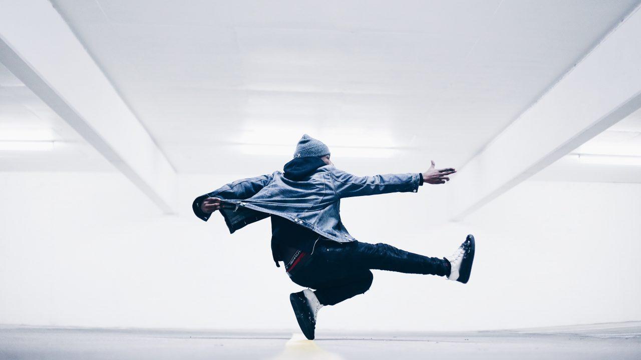 Mørkhudet mann som danser i en godt opplyst kjeller