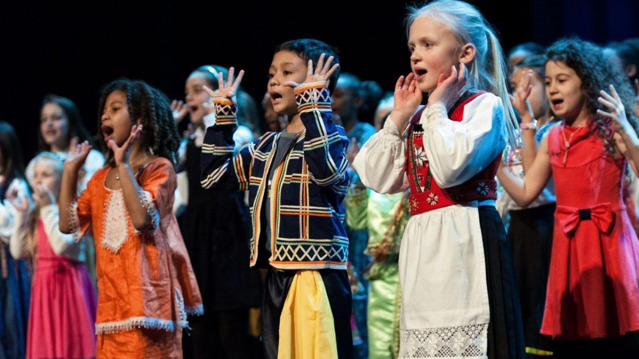 Barn med ulike nasjonaldrakter synger