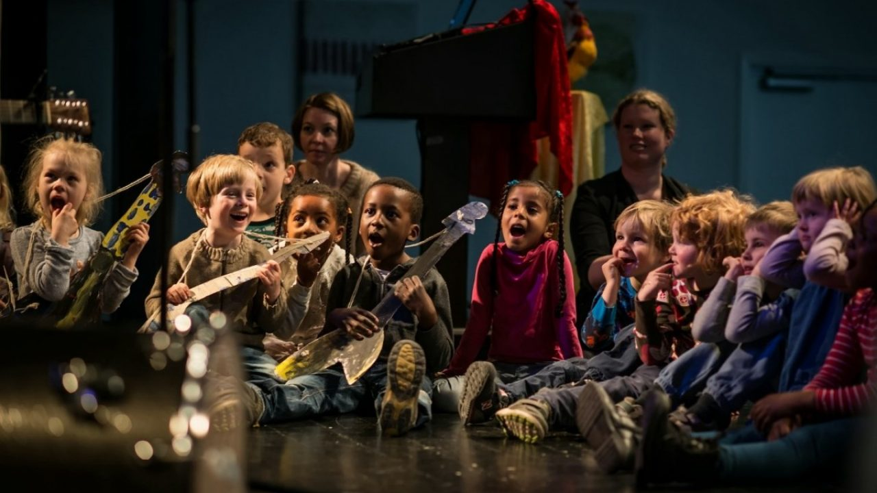 Barn synger og spiller på papirgitarer