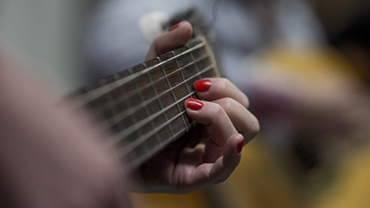 Hånd med røde negler spiller gitar