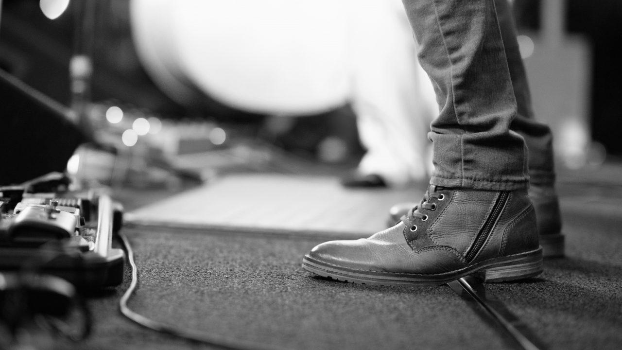 Scenegulv med musikkutstyr på et teppe, med to ben i forgrunnen