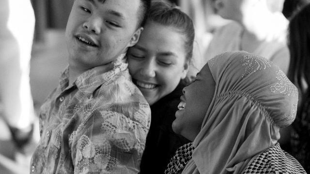 Tre elever smiler, holder rundt hverandre