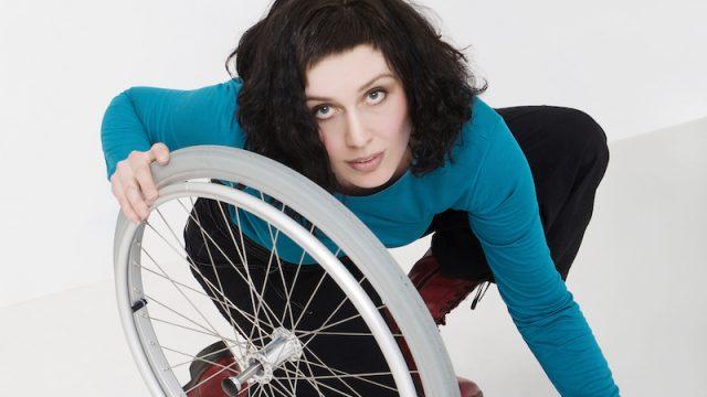 Dame med svart hår og blå genser. Holder et hjul