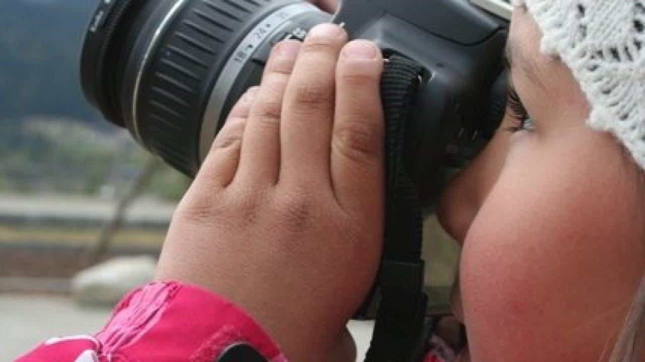 Jente som holder et kamera foran ansiktet.