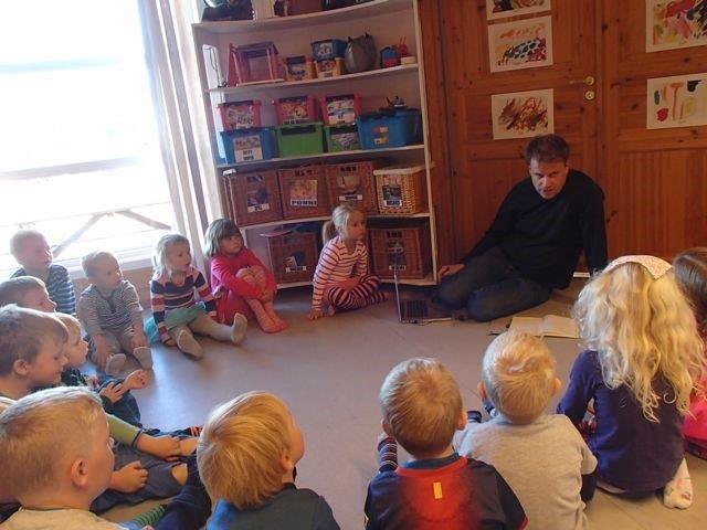 Barn og voksne sitter i en ring på gulvet.