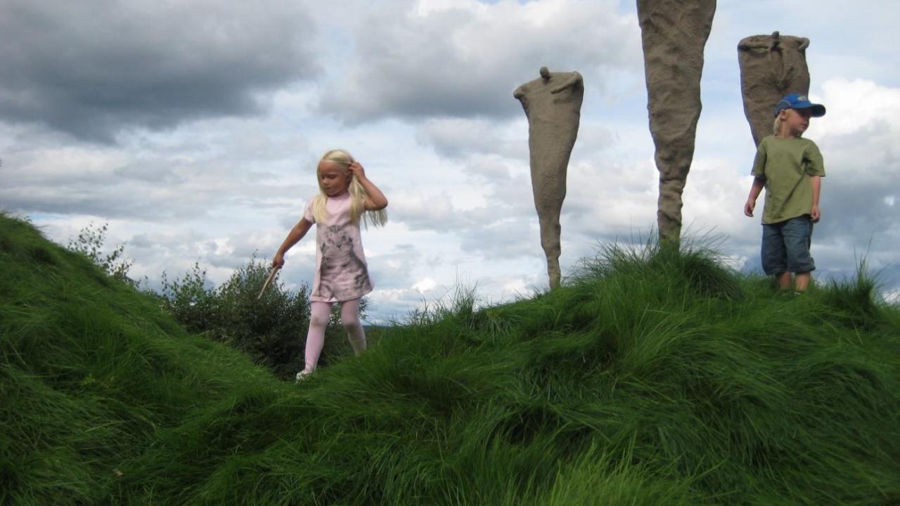 Barn løper på en eng, skulpturer i bakgrunnen.