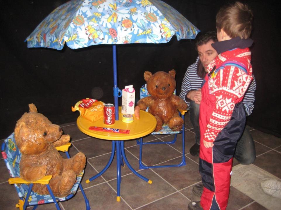 Barn og voksen studerer installasjon av bord, stoler og parasoll. teddybjørner sitter på stolene.