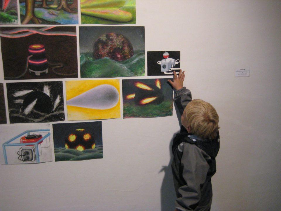 Barn studerer kunstutstilling på vegg.