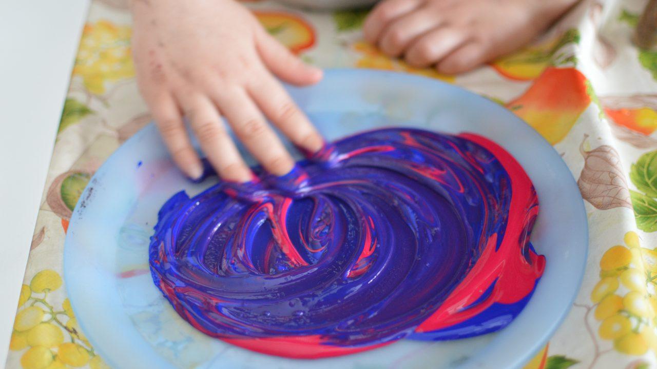 Barn maler med hendene og blander blå og rød farge.