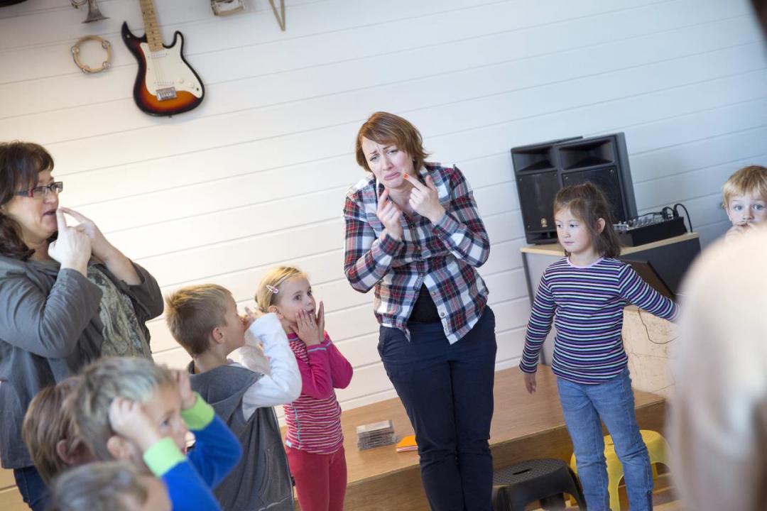 Voksen dame viser barn hvordan man ser lei seg ut.
