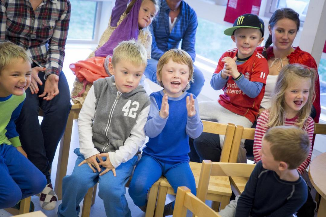Barn klapper og ler i publikum.