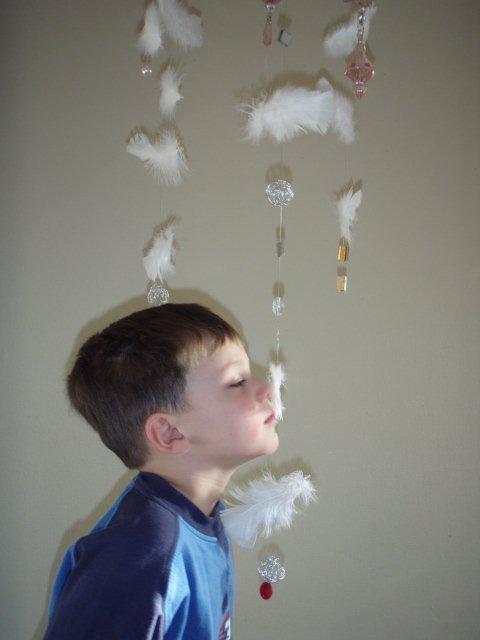 Gutt studerer fjær og lar den berøre ansiktet.