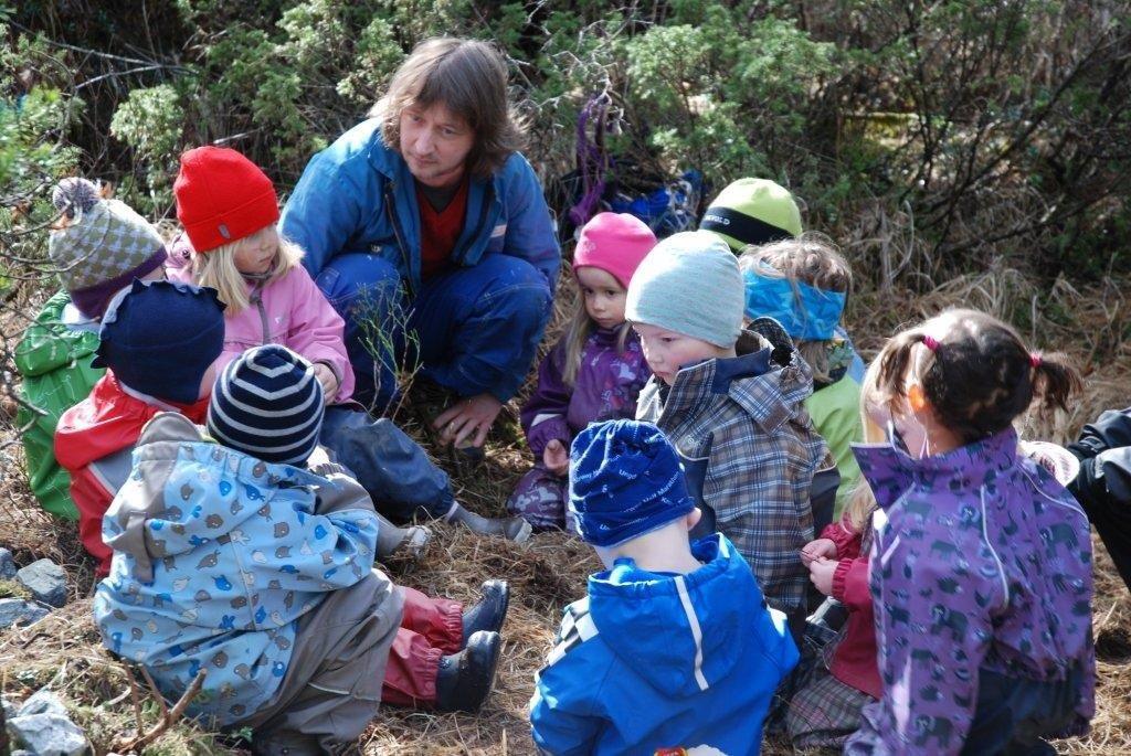 Barn og voksen sitter i en ring ute i naturen.