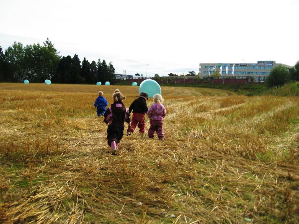 Barn løper på en eng med høyballer.