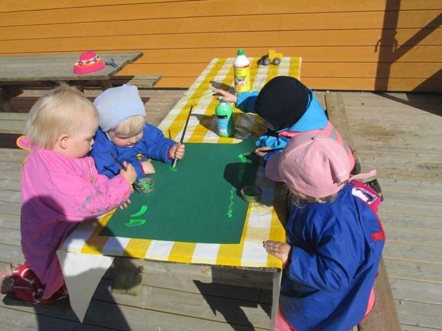 Barn samarbeider om maling ute ved et bord.