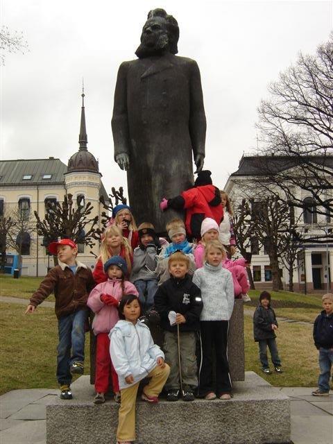 Barn foran Henrik Ibsen statue.