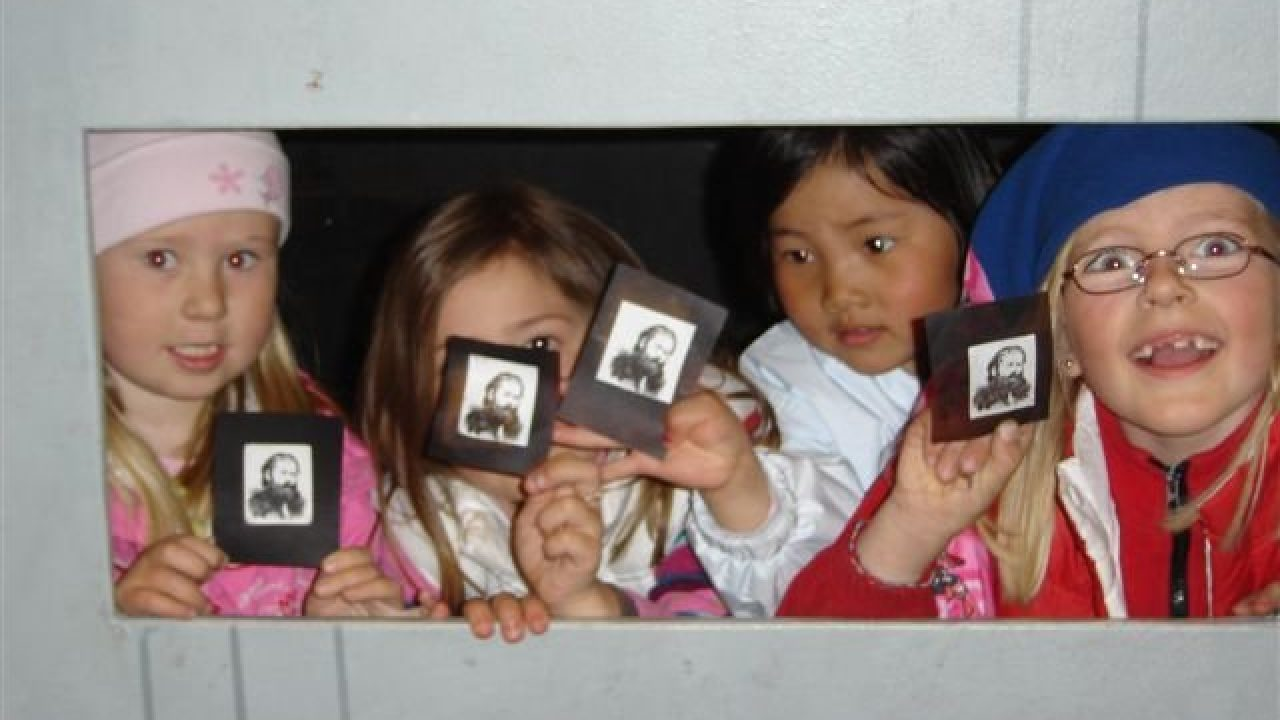 Barn holder opp små bilder av Henrik Ibsen.