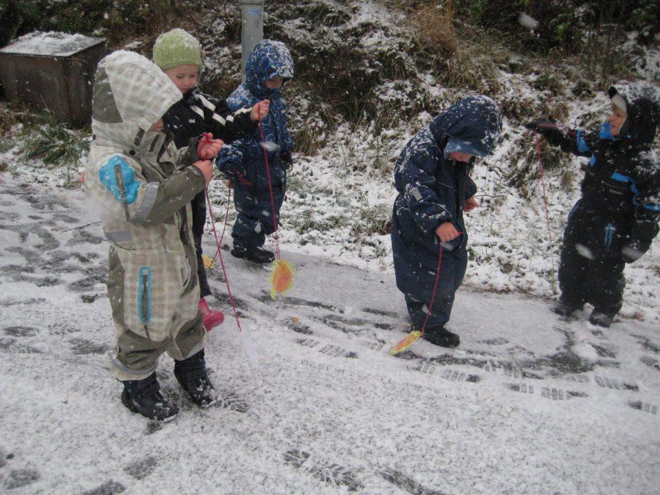 Barn går ute i snøen med lekeedderkopper hengende i en råd.