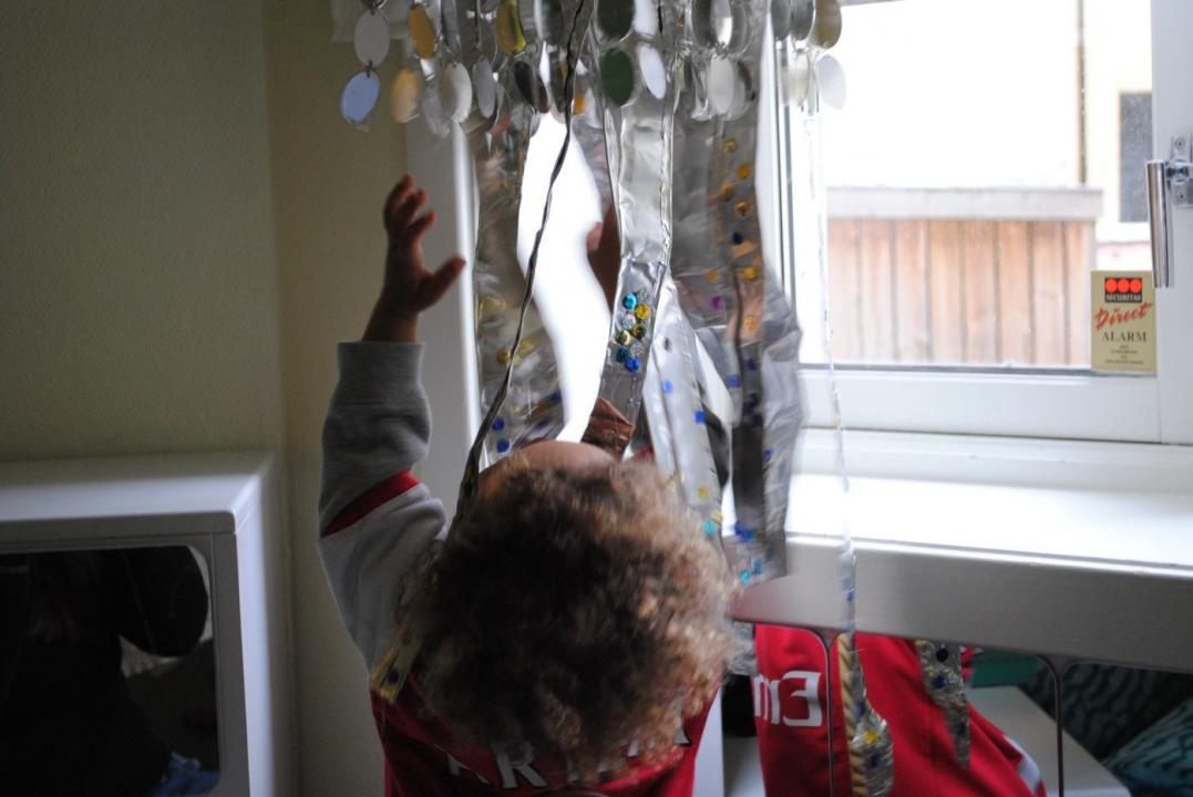 Barn står ved vindu og titter opp mot installasjon som henger i taket.