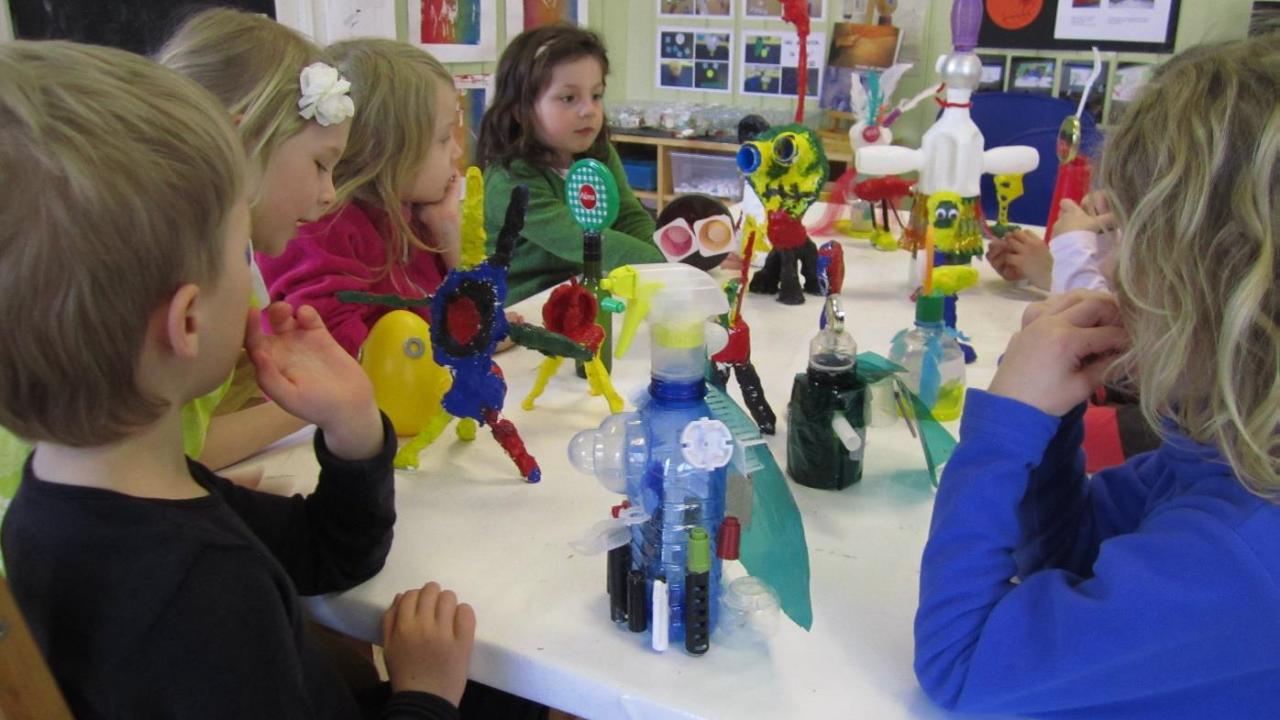 Barn lager skulpturer av gjenbruksmateriale og limpistol.