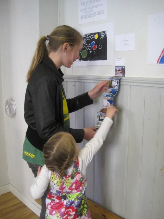 Barn og voksen studerer en remse med bilder som henger på en vegg.