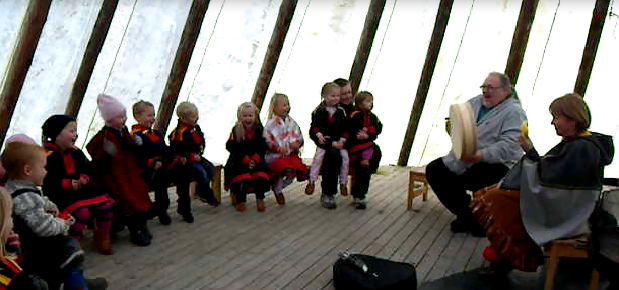 Barn og voksne som sitter i en lavvo og hører på musikk.