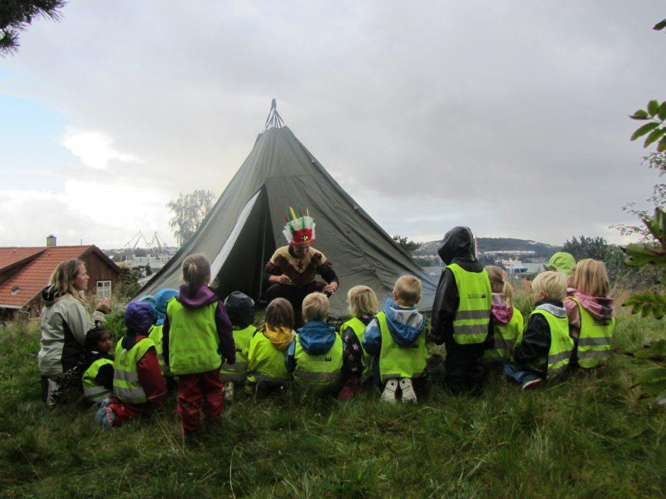 Barn og voksne sitter foran lavvo.