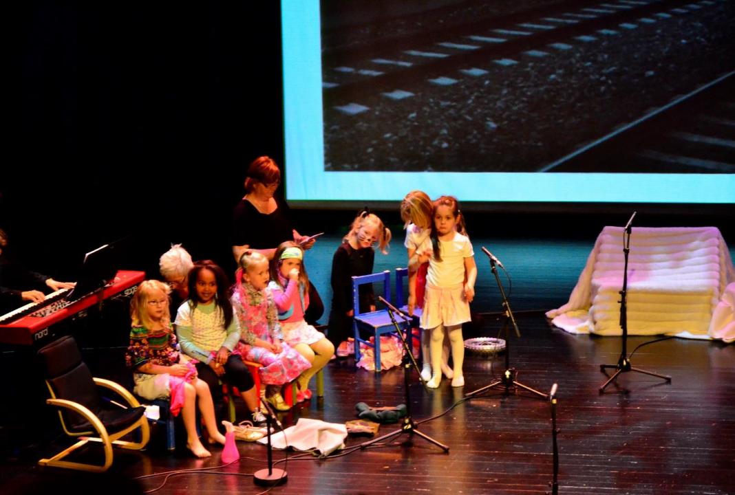 Barn synger på en scene.