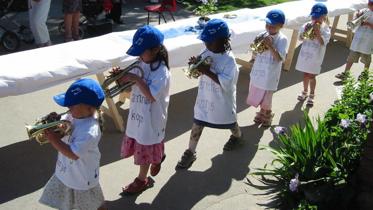 Barn marsjerer på rekke mens de spiller i korps.