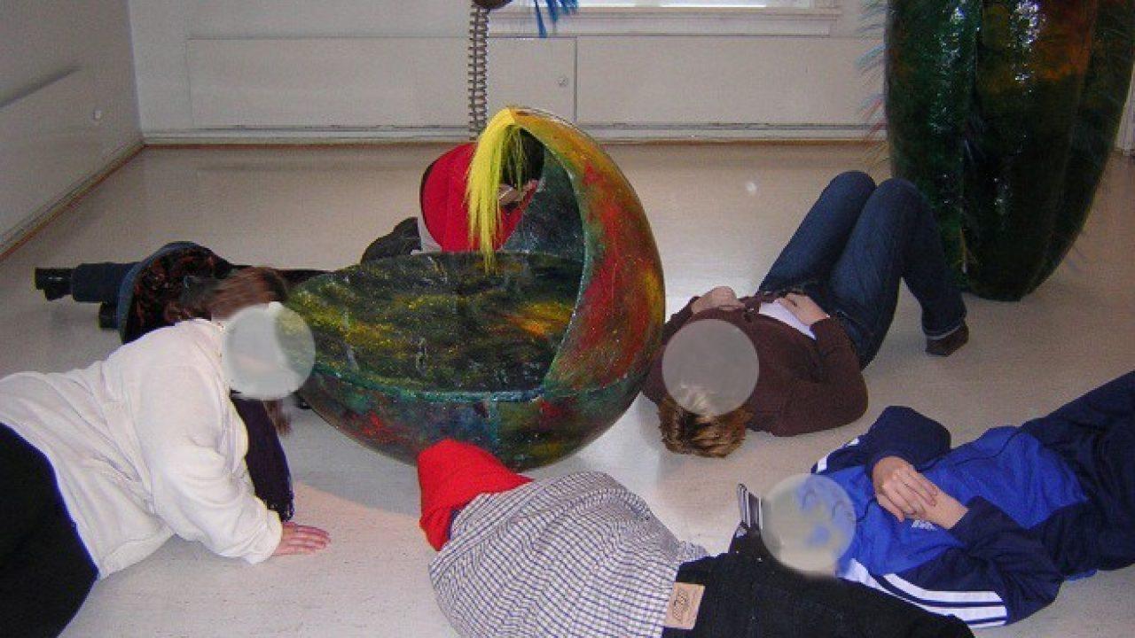 Elever ligger på gulvet og lytter rundt et rede av ull