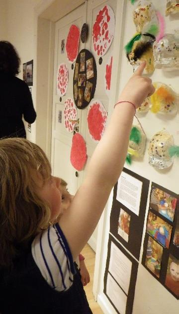 Barn ser på utstilling av barnehagens kunst.