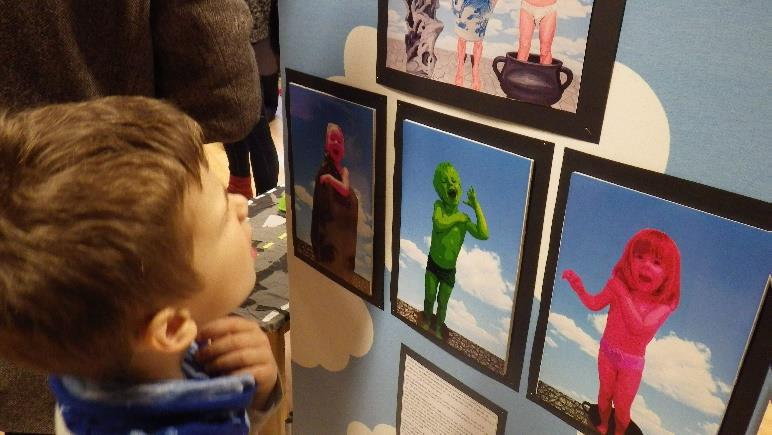 Barn studerer billedkunst som henger på en vegg.