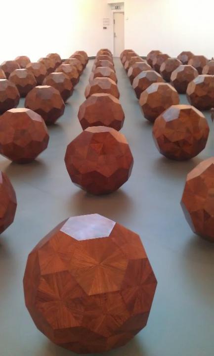 Kunstverk i kobbertoner, geometriske 3d figurer på linjer på gulvet.