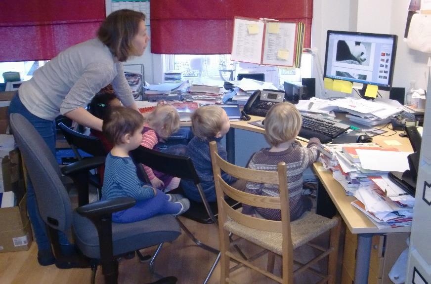 Barn sammen med en voksen på et kontor.