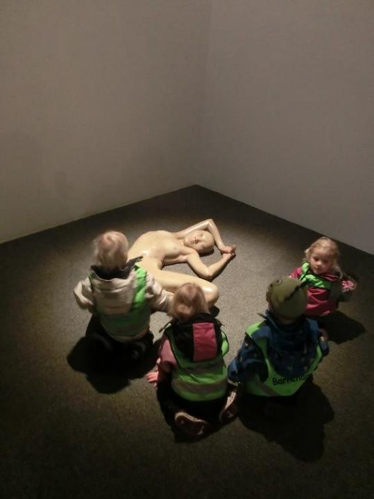 Barn studerer samtidskunst. Skikkelse ligger på gulvet.