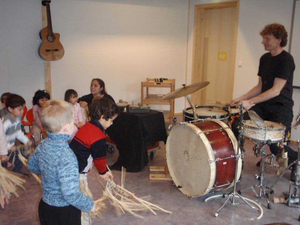 Barn eksperimenterer med instrumenter, voksen spiller trommer.