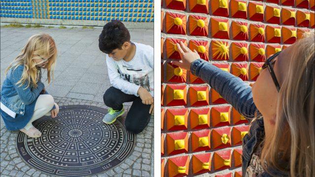 Gutt og jente finner et kumlokk og tar på en rød vegg