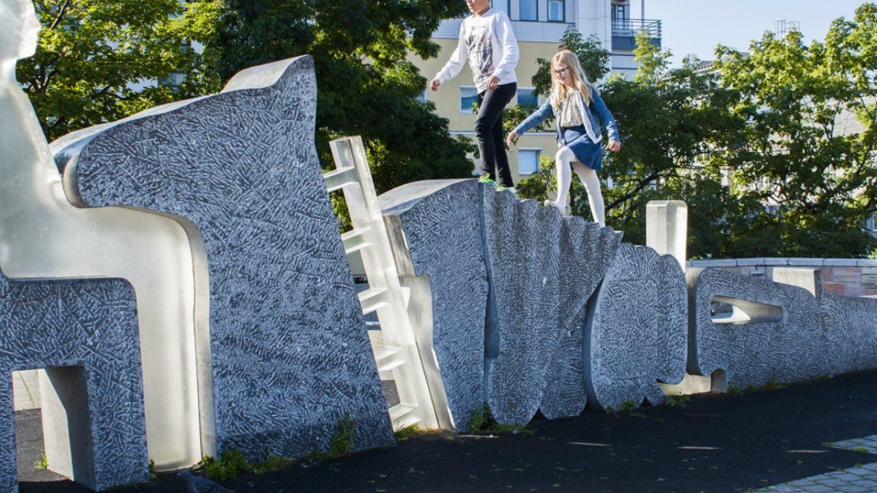 Gutt og jente går på en skulptur ute