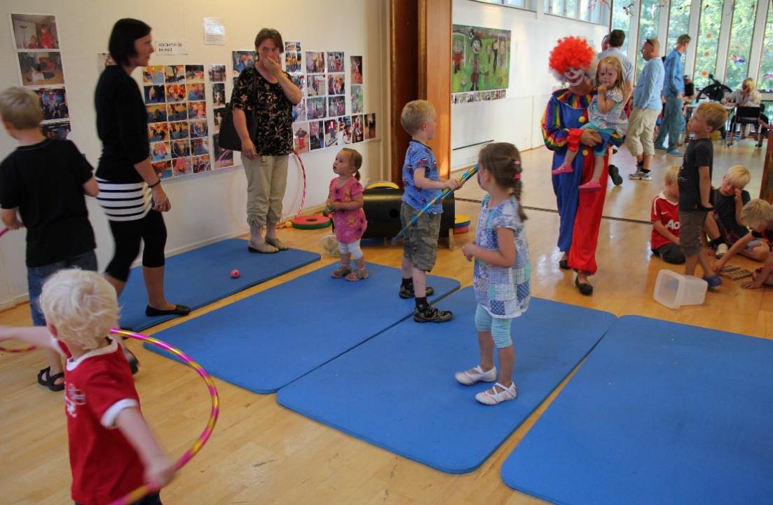 Blå gymmatter på et gulv, voksne og barn i lek.