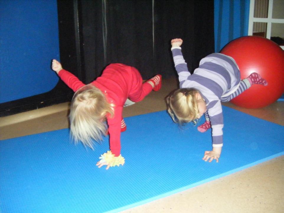 To barn står på blå matte med et bein og en hånd i bakken.