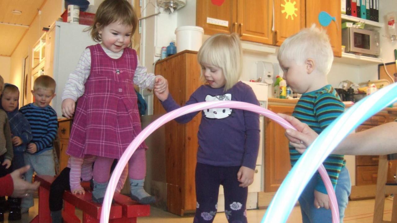 Et barn balanserer på en benk mens hun får hjelp av et annet barn.