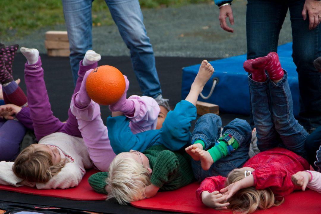 Barn ligger på matter og holder ball mellom beina.