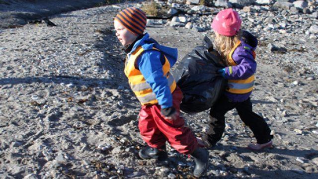 Barn i fjæra bærer svart søppelsekk mellom seg