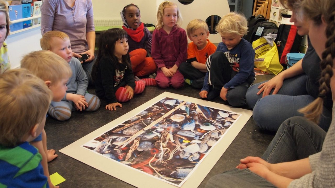 Barn i ring på golvet ser på et bilde