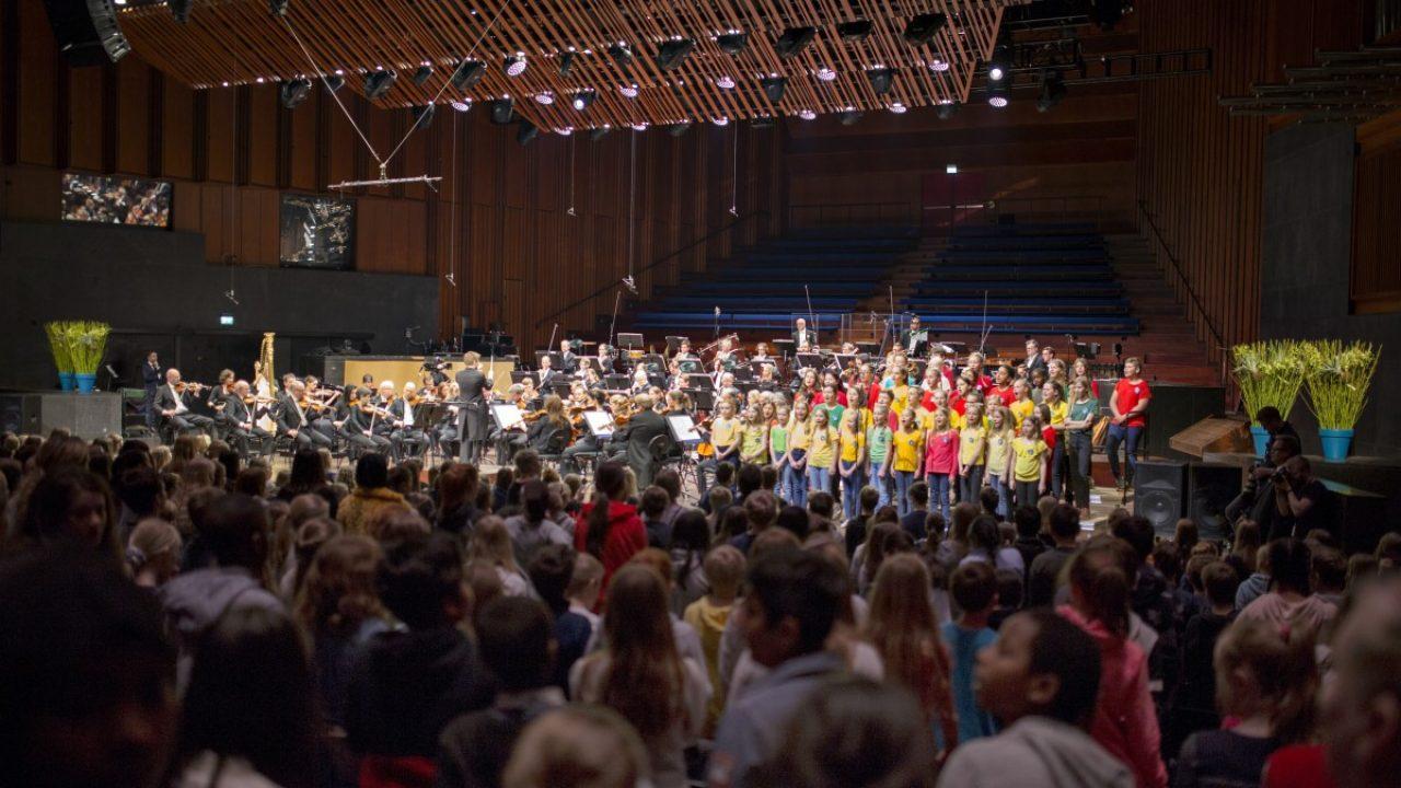 Bilde av en konsertsal med barn på en scene. Bildet er tatt fra publikumsplass.