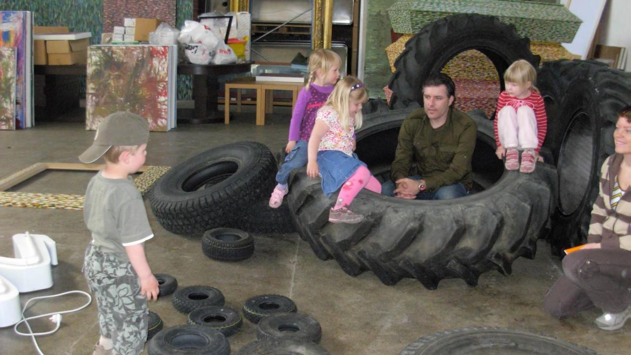 Barn og voksne sitter på trore dekk fra anleggsmaskiner.