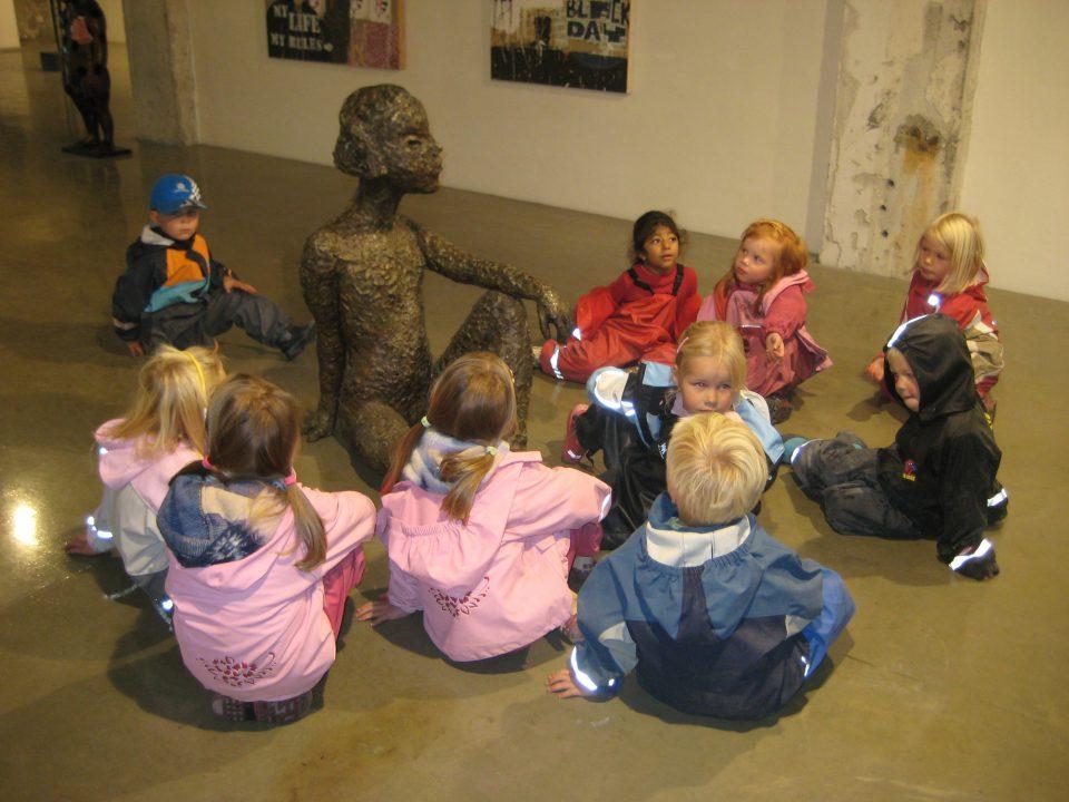 Barn betrakter skulptur på museum.